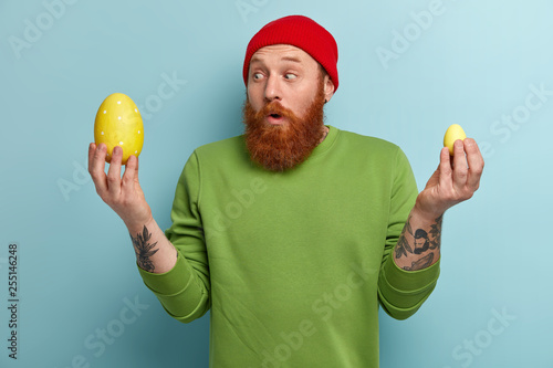 Photo Redhead surprised man prepares for great spring festival or Easter, carries two