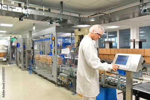 Photo  Arbeiter in Schutzkleidung am Fliessband für den Versand Pakete von verpackten M