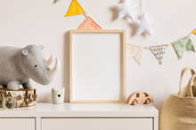 The Modern Scandinavian Newborn Baby Room With Mock Up Photo Frame, Wooden Car, Plush Rhino And Clouds. Hanging Cotton Flags And White Stars. Minimalistic And Cozy Interior With White Walls.Real Photo