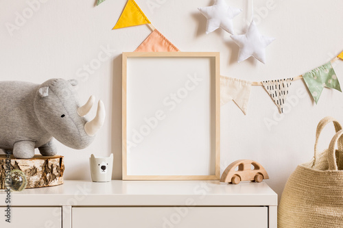 Obraz The modern scandinavian newborn baby room with mock up photo frame, wooden car, plush rhino and clouds. Hanging cotton flags and white stars. Minimalistic and cozy interior with white walls.Real photo - fototapety do salonu