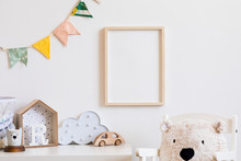 Stylish Scandinavian Child Room With Mock Up Photo Poster Frame On The White Wall. Cute Modern Interior Of Nursery With Boxes, Teddy Bear, Toys.  Wooden Accessories And Colorful Flags. Real Photo.