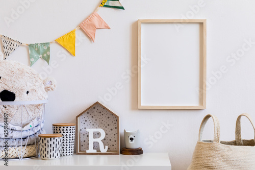 Foto  Stylish scandinavian child room with mock up photo poster frame on the white wall
