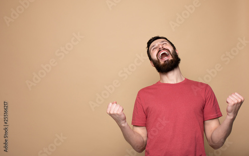 Valokuva  Image of a handsome happy excited bearded man posing isolated over beige wall background make winner gesture