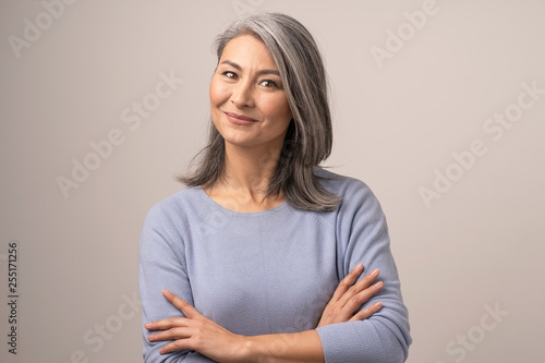 Tela Smiling Asian senior woman with crossed arms
