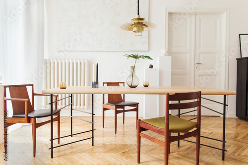Fotografie, Tablou  Eclectic and elegant dining room interior with design sharing table, chairs, gold pedant lamp, abstract paintings, piano and stylish accessories