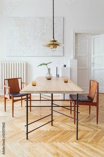 Fotografija Eclectic and elegant dining room interior with design sharing table, chairs, gold pedant lamp, abstract paintings and stylish accessories