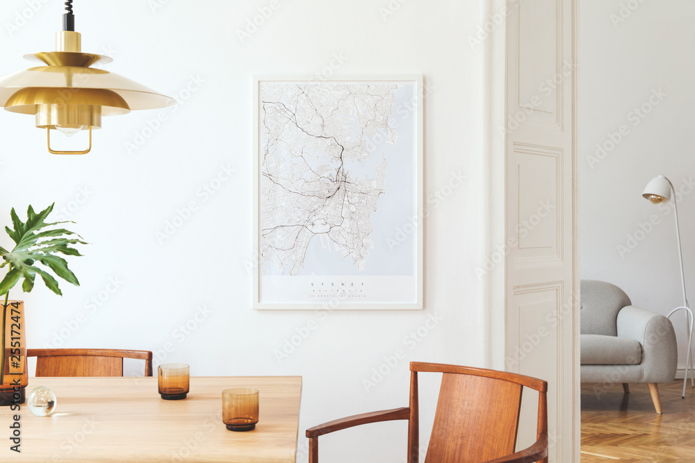 Fototapeta Stylish and eclectic dining room interior with mock up poster map, sharing table design chairs, gold pedant lamp and elegant sofa in second space. White walls,  wooden parquet. Tropical leafs in vase.