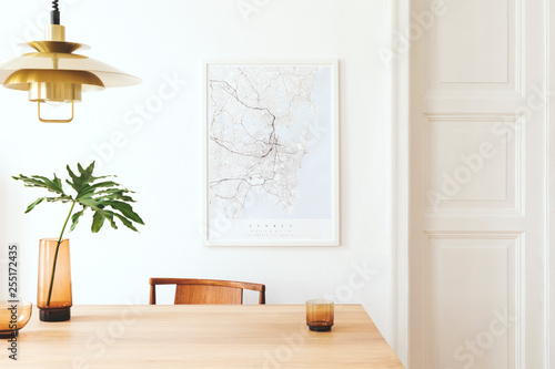 Stylish and modern dining room interior with mock up poster map, sharing table design chairs, gold pedant lamp and cups of coffee Slika na platnu