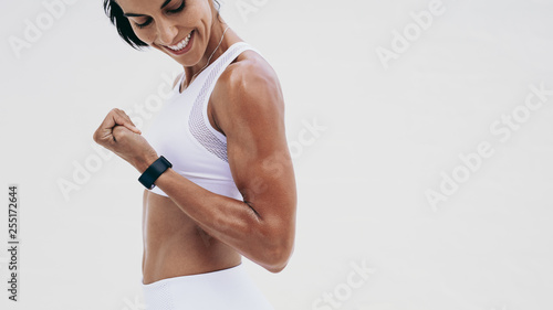 Foto Close up of a smiling fitness woman looking at her hand