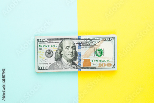 100 US dollar bill money cash on blue and yellow background Canvas Print