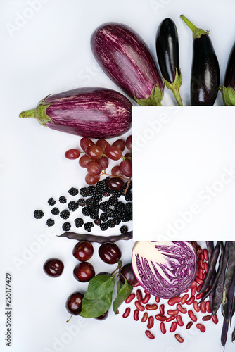 Raw violet vegetables and fruit on white background.