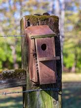 Birdhouse On A Fence Post.