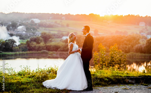 Fotografia  Man and woman reach out their hands while standing in the rays sunny