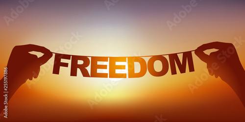 Concept de l'esprit libre, avec deux mains qui tiennent une guirlande sur laquelle est écrit le mot liberté devant un ciel ensoleillé Canvas-taulu