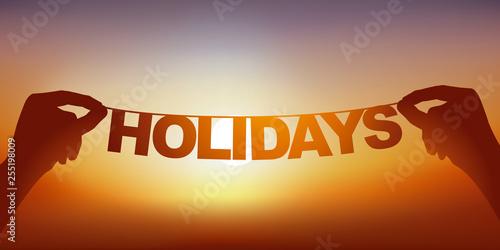 Valokuva  Concept du bonheur de partir en vacances avec deux mains qui tiennent une guirlande sur laquelle est écrit le mot vacances devant un ciel ensoleillé