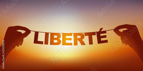 Valokuva  Concept de l'esprit libre, avec deux mains qui tiennent une guirlande sur laquelle est écrit le mot liberté devant un ciel ensoleillé