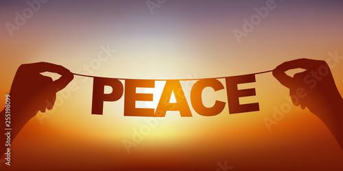 Concept de la paix et la tranquillité, avec deux mains qui tiennent une guirlande sur laquelle est écrit le mot paix, devant un ciel ensoleillé Canvas-taulu