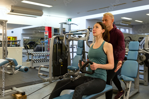 Young beautiful woman doing exercises with personal trainer. Young adult personal fitness trainer supporting his client at gym