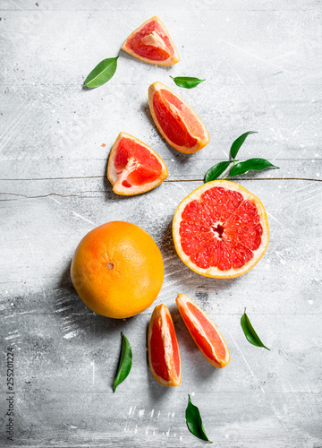 Fotografia  Pieces of grapefruit with leaves.