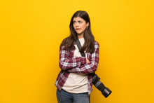 Photographer Teenager Girl Over Yellow Wall With Confuse Face Expression While Bites Lip
