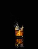 Fototapeta Sawanna - Isolated shot of whiskey with splash on black background