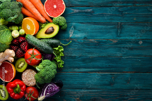 Obraz Healthy organic food on a blue wooden background. Vegetables and fruits. Top view. Free copy space. - fototapety do salonu