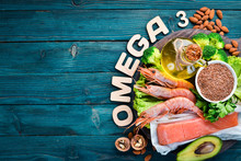 Foods Containing Omega 3. Vitamin Healthy Foods: Avocados, Fish, Shrimp, Broccoli, Flax, Nuts, Eggs, Parsley. Top View. Free Space For Your Text. On A Blue Wooden Background.