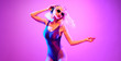 canvas print picture - Shapely fashionable DJ girl dance enjoy music in colorful neon uv purple light. Rave house music night club vibes. High Fashion. Young blonde model woman relax enjoy dancing, neon makeup.