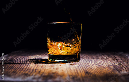 Pinturas sobre lienzo  whiskey with ice cubes on wooden background