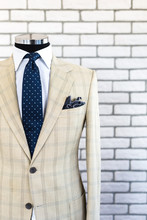 Expensive Custom Tailored Suit On Male Mannequin With Urban Trendy Colors Isolated On Brick Background
