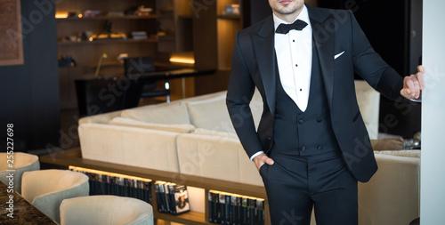 Man model in expensive custom tailored tuxedo, suit standing and posing indoors Fototapeta