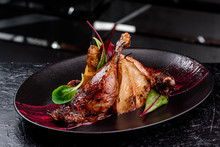 Exclusive Restaurant Meals. Duck Confit With Baked Pear And Cranberry Sauce Served On Snow Dark Plate On Black Table Background. Copy Space