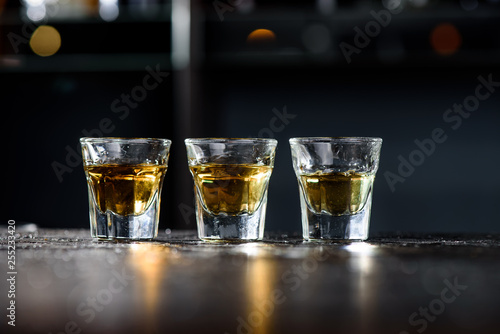 Obraz na plátně  Three glasses of whiskey on a dark wooden bar in a nightclub