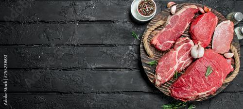 Fototapeta Raw meat. Pork and beef steaks on a tray with spices and rosemary sprig. obraz na płótnie