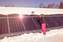 Woman Pushing Snow Off Solar Panels In Winter. If Snow Covering Cell Panels, They Can't Produce Power. Warm Filter, Lens Flare, Sunny Day, Clear Blue Sky.