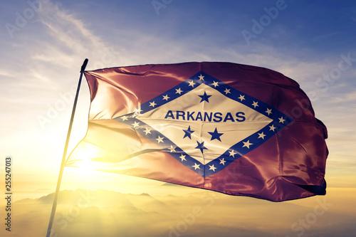 Arkansas state of United States flag waving on the top sunrise mist fog Canvas Print