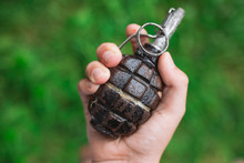 Closeup Top View Of White Kid Hand Holding Real Old Grenade. Horizontal Color Photography.