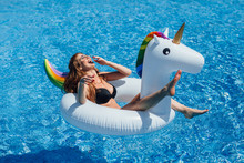 Young Beautiful Brown-haired Girl With A Good Figure Tan In The Pool On An Inflatable Unicorn In A Black Swimsuit.