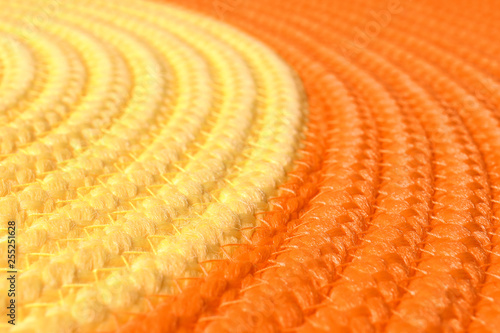 Orange and yellow wicker mat texture as background, closeup