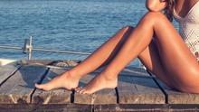 Beautiful Tanned Young Woman Legs Sit On Wooden Sea Dock Sunny Summer