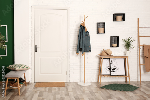 Foto Stylish hallway interior with shoe storage bench, hanger stand and table