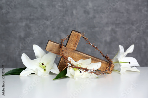 Fotografie, Obraz  Wooden cross, crown of thorns and blossom lilies on table against color backgrou