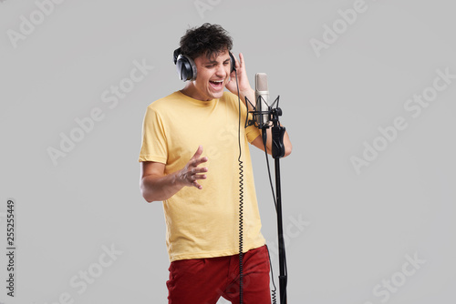Canvas Print Portrait of rock singer man in studio professional headphones keeping static mic, sings a song loudly on grey background
