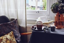 Cozy Home With Cup Of Tea With Steam, Blanket, Book And Candles. Hygge Home Interior