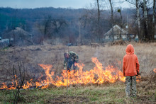The Child On The Background Of Fire. Burning Grass On The Field In The Village. Burning Dry Grass In The Fields. Danger Of Fire From Careless Behavior With Fire.