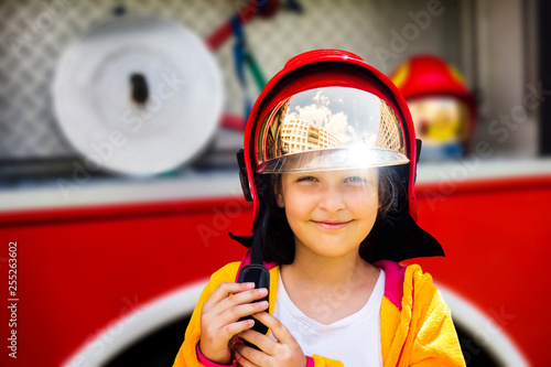 Cute young girl trying on real fireman's helmet standing in front of firetruck Canvas Print