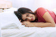 Attractive cheerful young woman lying down with white pillow after wake up on white bed looking at camera. Lifestyle concept