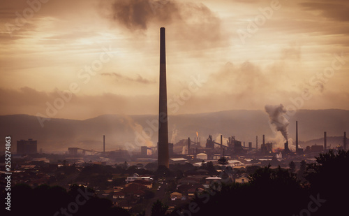 High view across industrial town to steel works and smoke stacks on stormy atmospheric evening. Old industries, climate change and global warming concept.