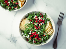 Vegan Salad Bowl With Arugula, Pear, Pomegranate, Coconut Crumble Or Cottage Cheese On Marble Tabletop. Vegan Breakfast, Vegetarian Food, Diet Concept. Top View Or Flat Lay.