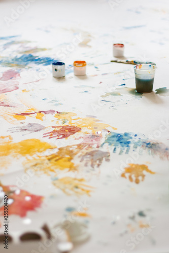 Fototapety, obrazy: Child's hand prints on paper, drawing with fingers, paint cans. Selective focus